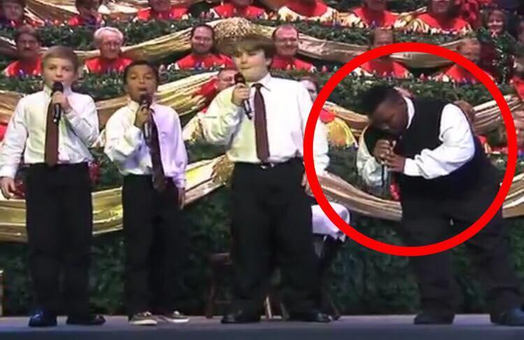 4 drenge går op på scenen - da drengen til højre begynder at synge bryder salen ud i et stort latterbrøl
