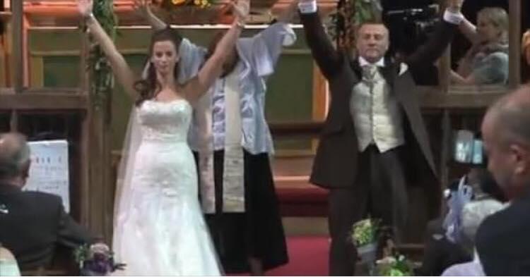 Brudeparret vender sig pludseligt om, og rækker begge hænder i vejret - årsagen gør alle tomme for ord